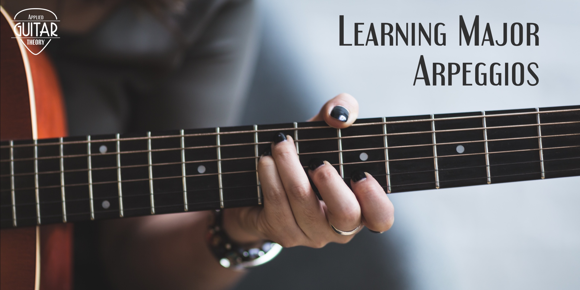 Female playing major arpeggio on guitar