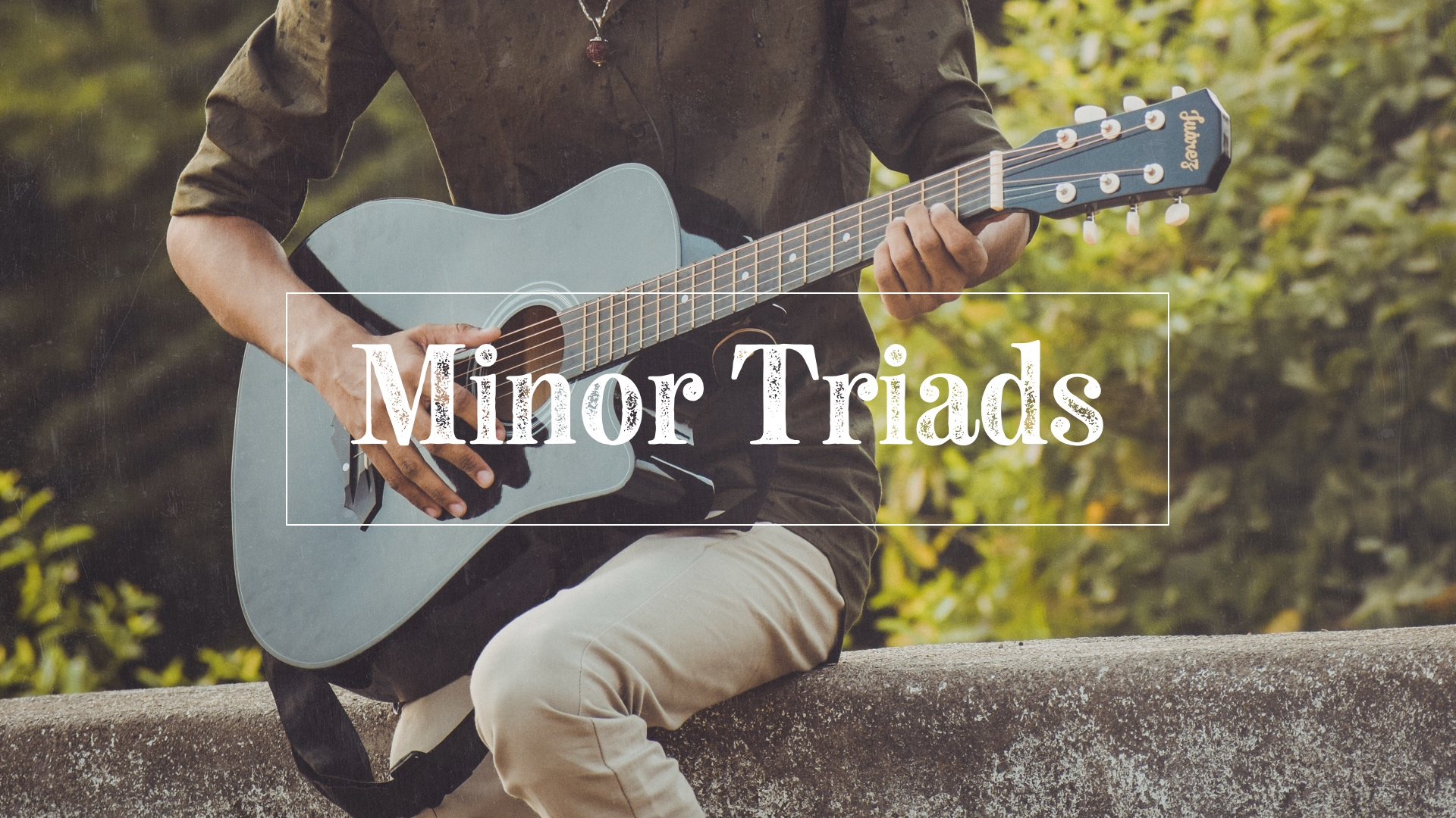 Guy learning minor triads on guitar